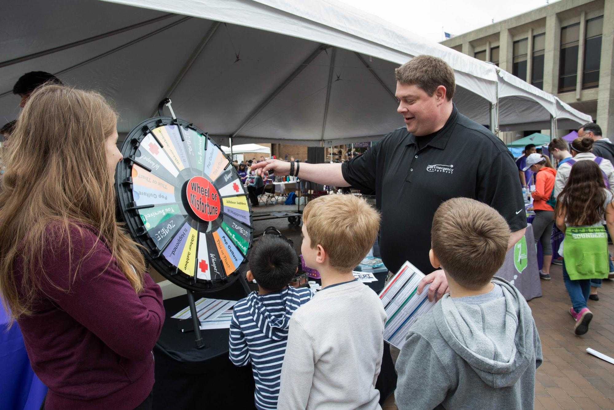 """Scott Preston from UW Emergency Management helps kids spin the """"Wheel of Misfortune"""""""