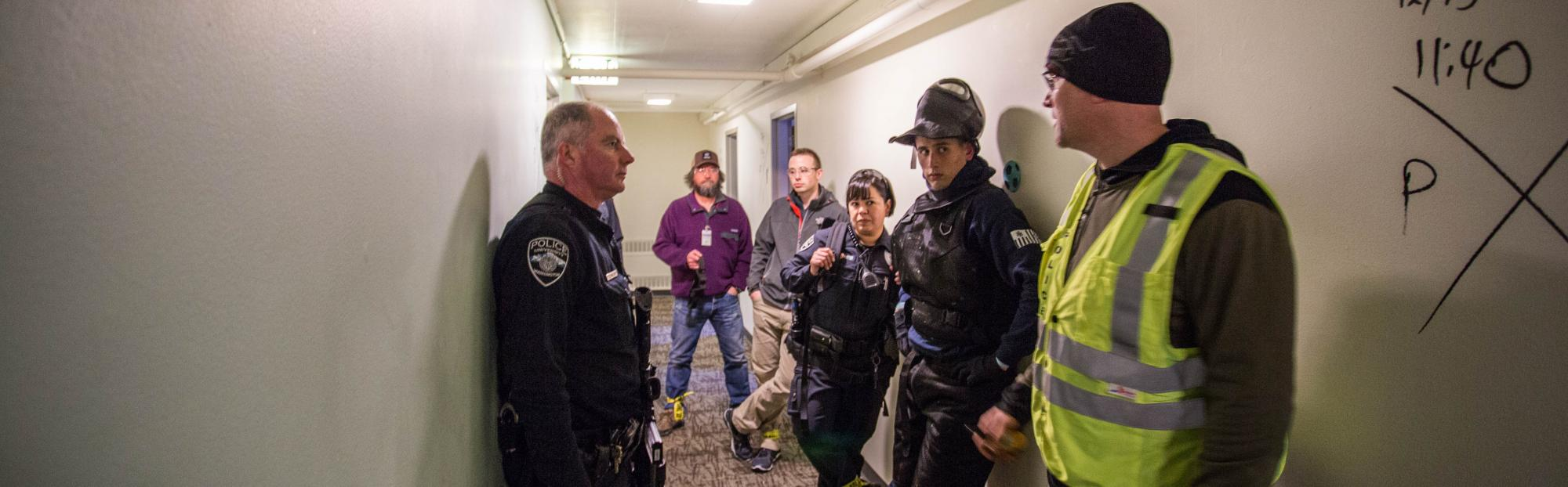UWPD officers and volunteers debrief after an active shooter training exercise in the empty McCarty Hall.