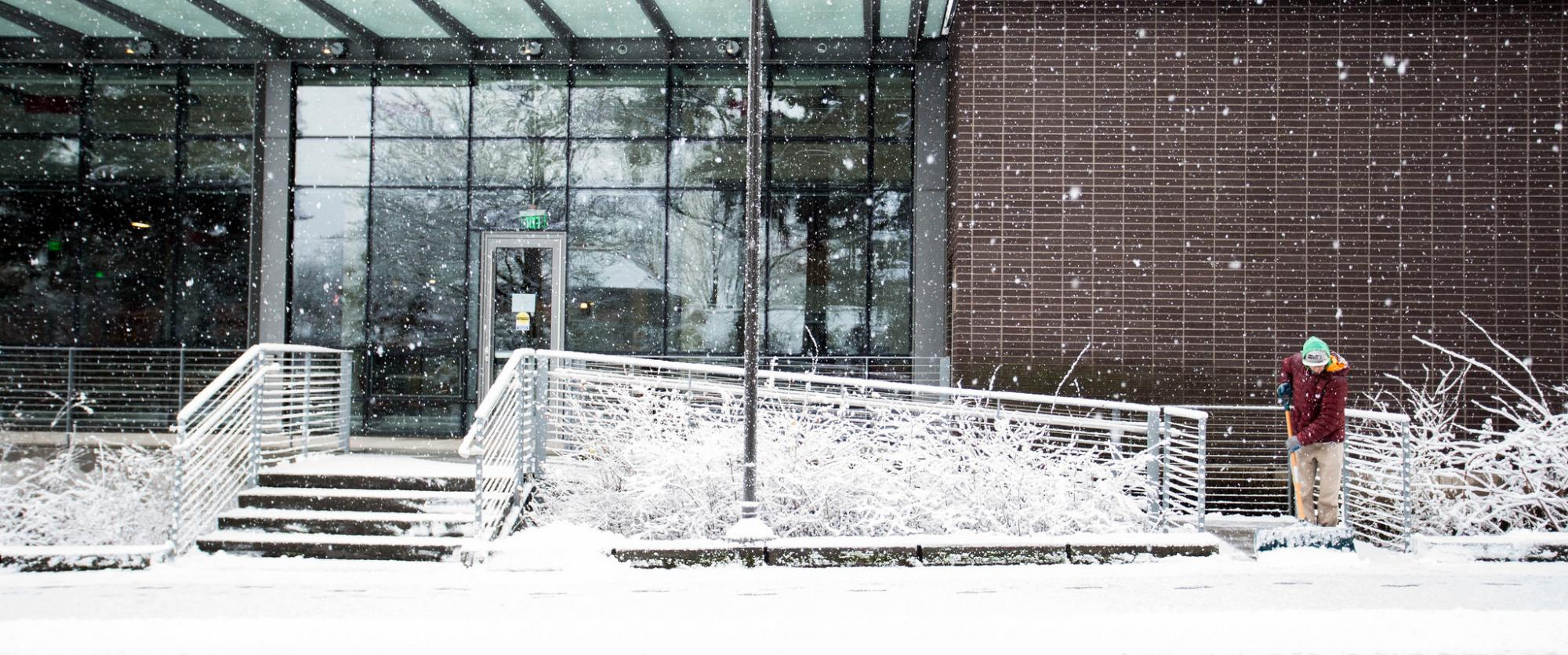 An employee clears a path outside of the Husky Student Union Building (HUB).
