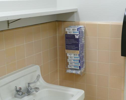 Dispenser container stocked with feminine products mounted to tiled wall in restroom
