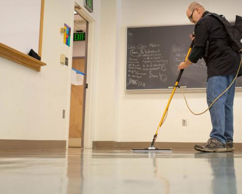 Custodian William (Bill) Garl waxes floors in the Chemistry Library