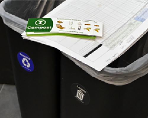 Two public area bins with a stack of compost labels sitting on top.