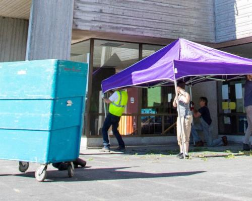 Employees setting up donation station outside of a residence halls for students to drop off donations.