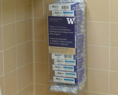 A clear acrylic dispenser affixed to a tiled wall holds individually-wrapped tampons and pads