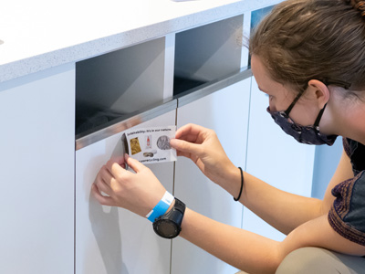 person affixing a label to a recycling container indoors