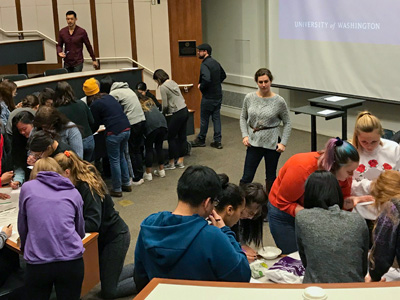 students in a lecture hall working in separate groups with a presentation up on screen