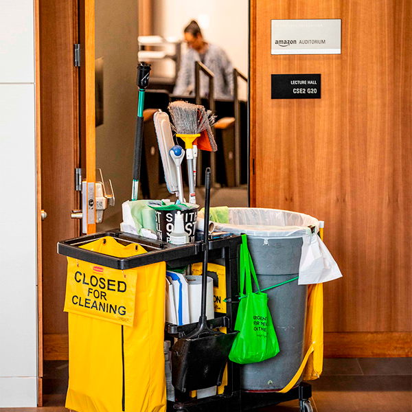 custodian cleaning cart with a person in the background