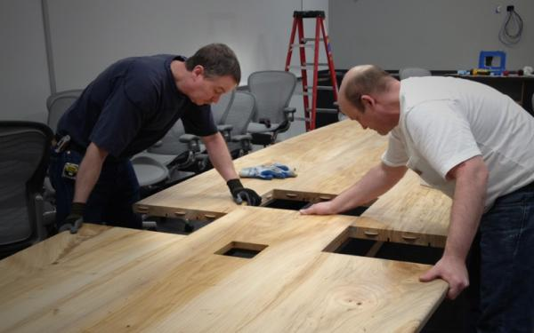two carpenters putting hand crafted pieces of a conference room table together