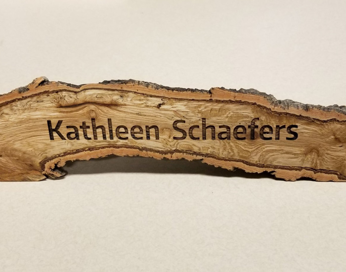 wood branch split and finished with name engraved on surface