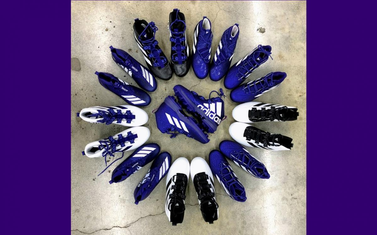 ten to twelve pair of athletic cleats displayed in an attractive circle pattern on a cement floor