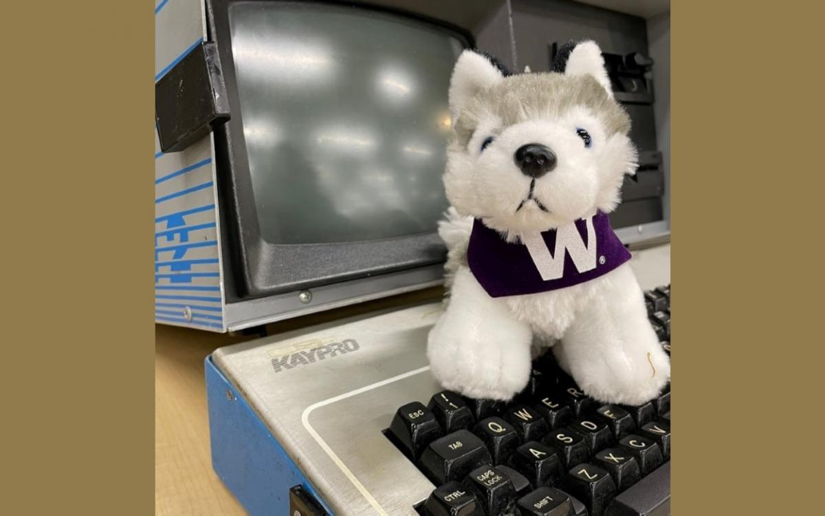 Small toy Husky sits on old Kaypro2 computer keyboard