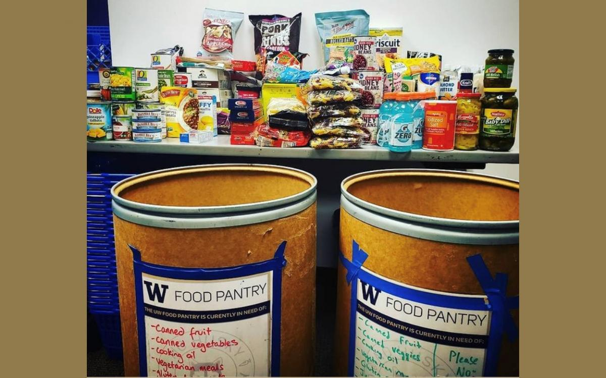 Two barrels sit next to a shelf that is full of non-perishable foods