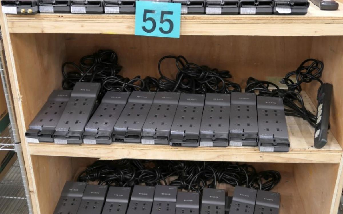 Lot 55 is made up of various surge protectors on a cart