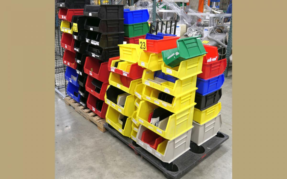 multi-colored bins stacked on a dolly